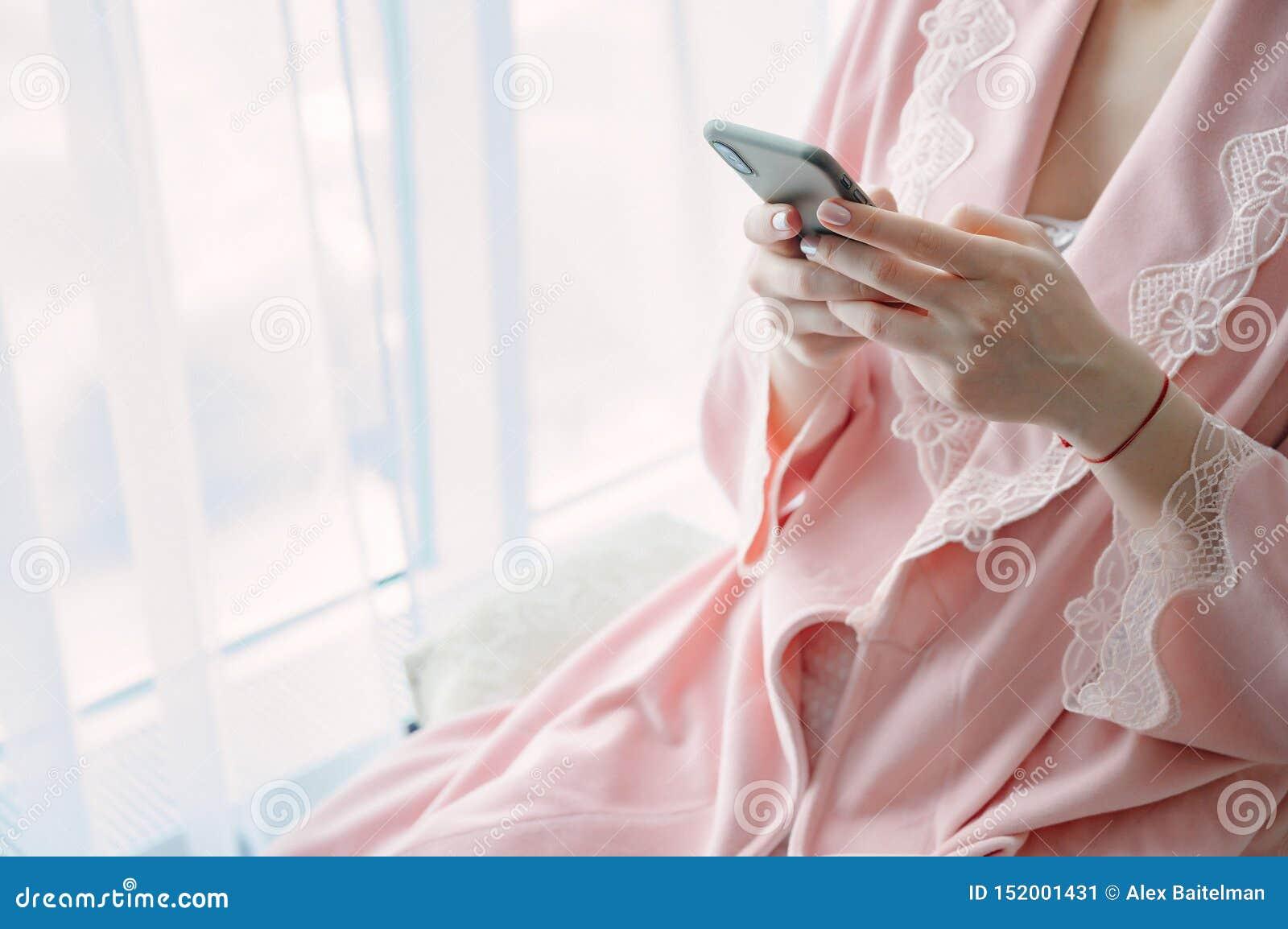 Mujer joven en ropa interior con un teléfono móvil