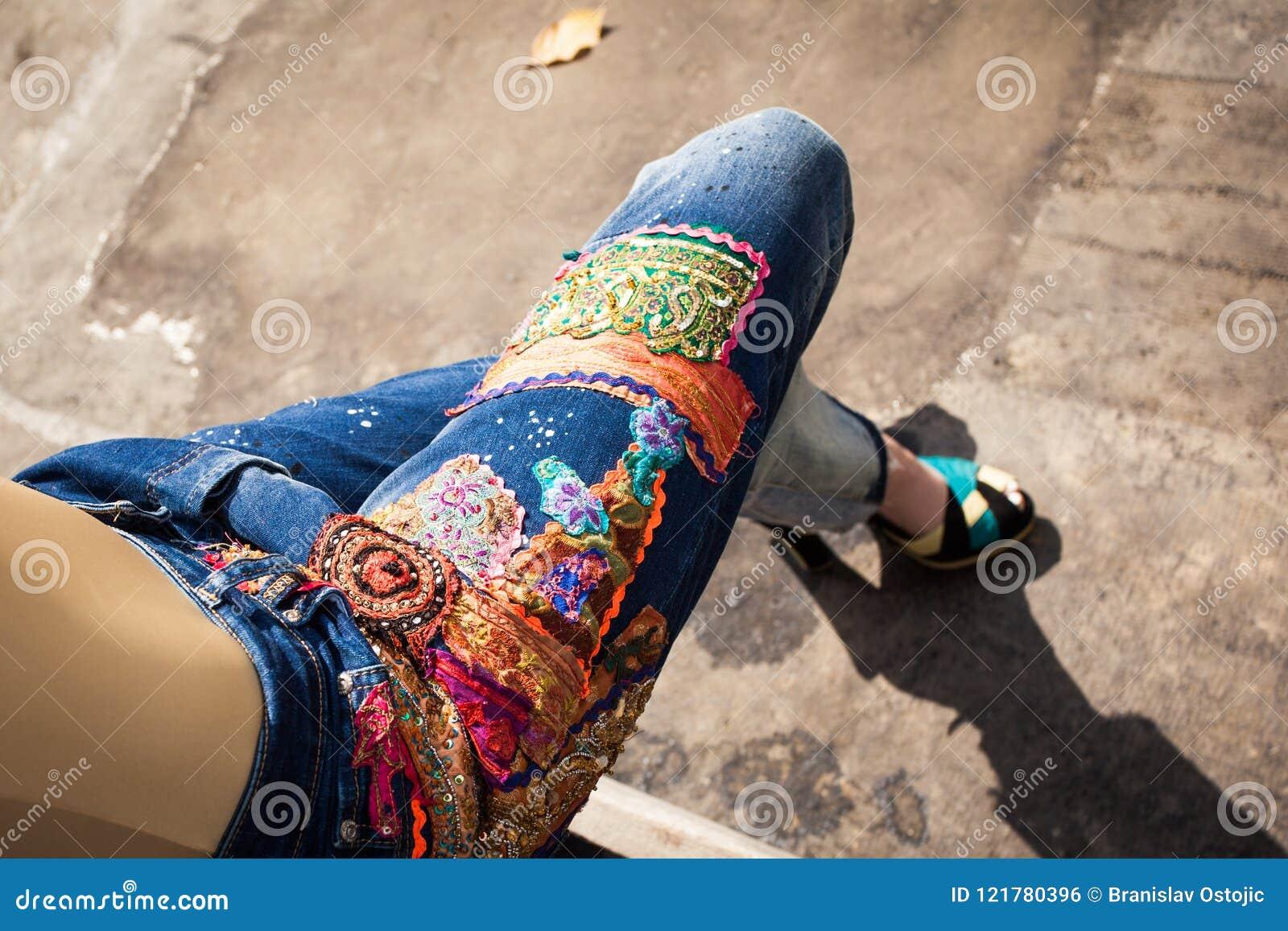 Mujer joven en tejanos y tacones altos en molestia del verano del patio trasero