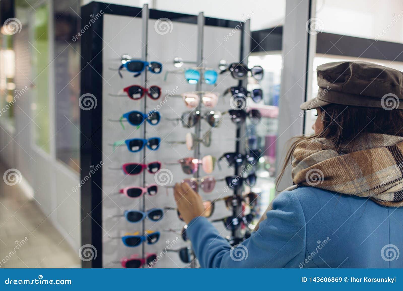 Mujer joven en tienda óptica - la muchacha hermosa elige los vidrios en tienda del óptico