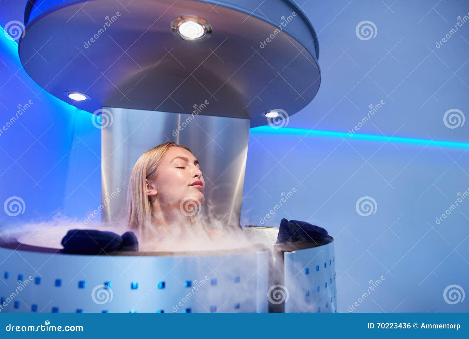 Mujer joven en una sauna del cryo del cuerpo entero