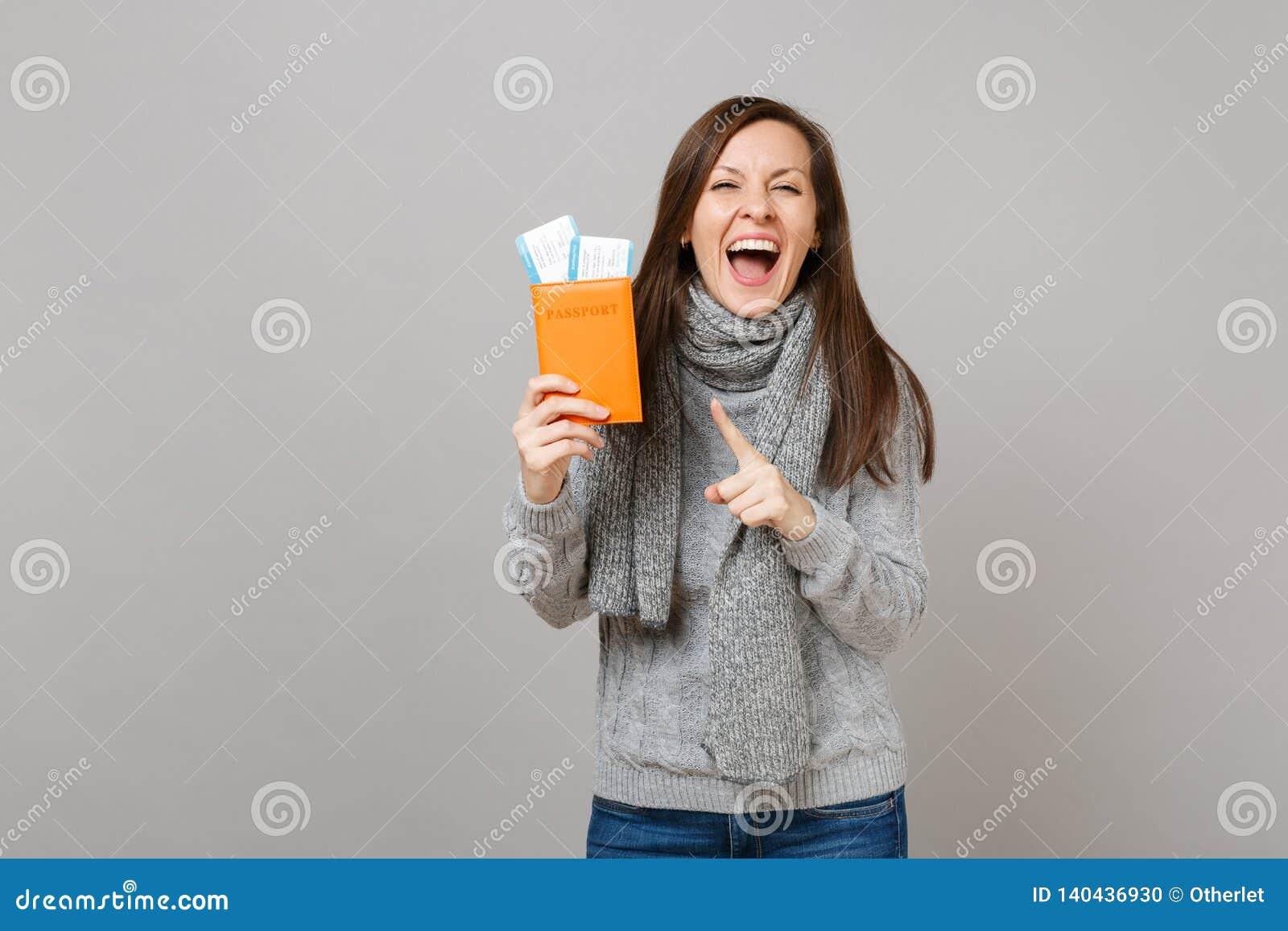 Mujer joven extática en el suéter gris, bufanda señalando el dedo índice en el boleto del documento de embarque del pasaporte ais