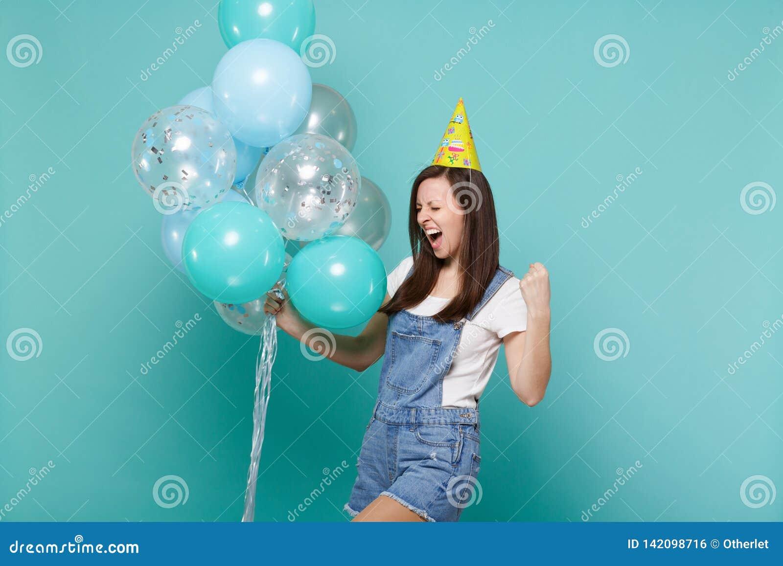 Mujer joven extática en sombrero del cumpleaños que grita haciendo el gesto del ganador, celebración, celebrando los balones de a