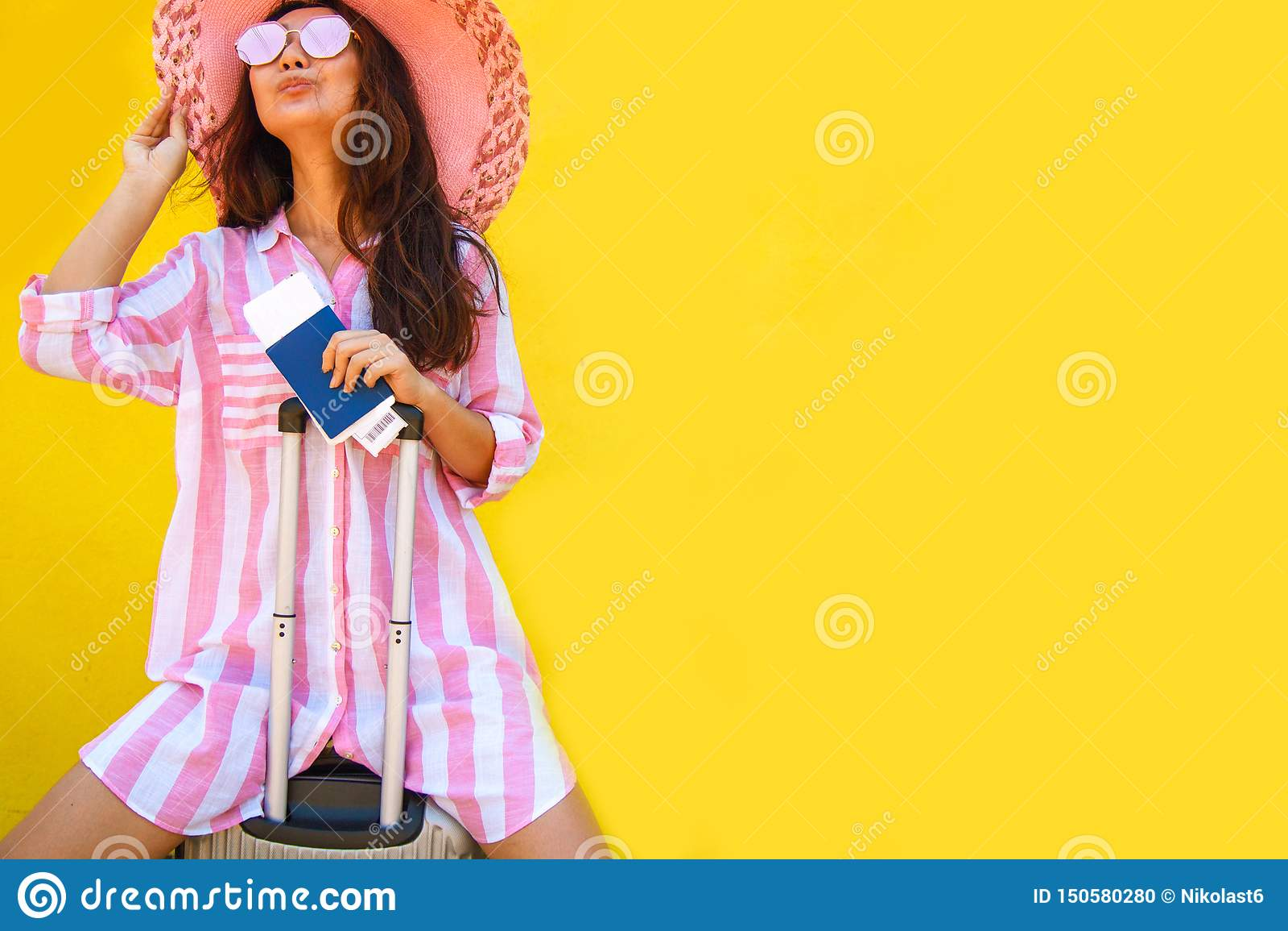 Mujer joven extática feliz en la maleta que se sostiene rosada, boleto del documento de embarque del pasaporte aislado en fondo a
