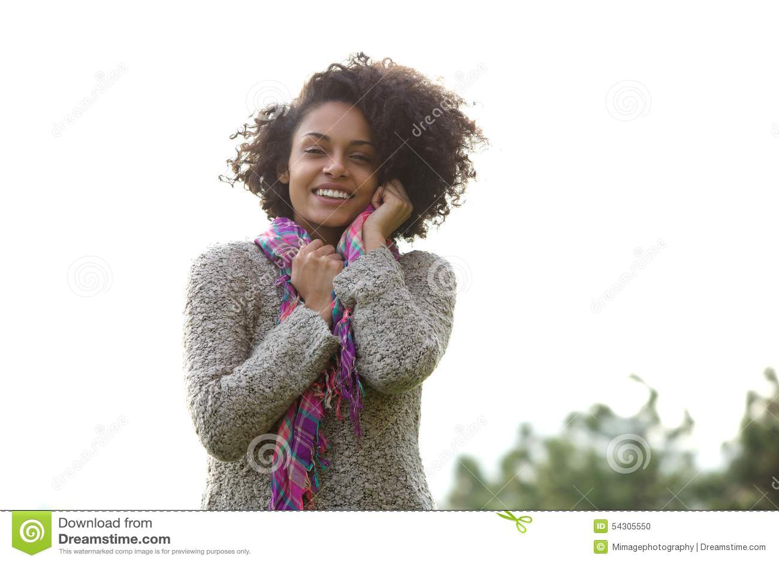 Mujer joven feliz de la raza mixta que sonríe al aire libre