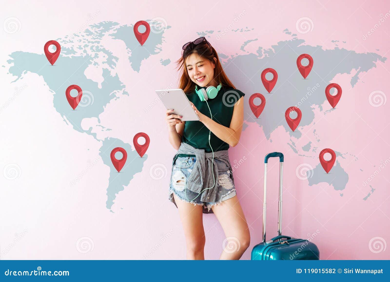 Mujer joven feliz del viajero que se coloca con la maleta y que usa Tabl