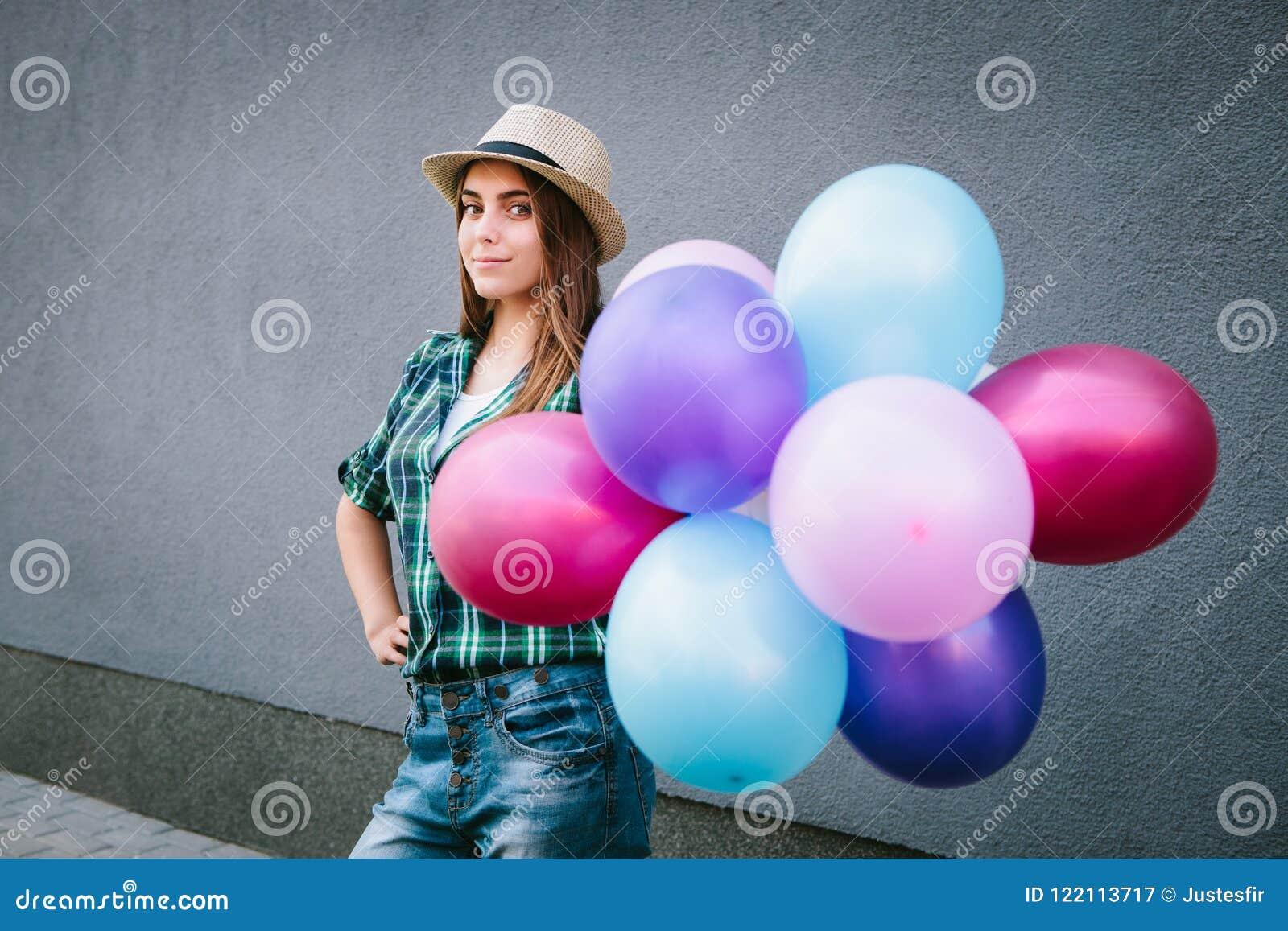 Mujer joven feliz en la camisa y el sombrero de tela escocesa que se colocan con los globos y la sonrisa