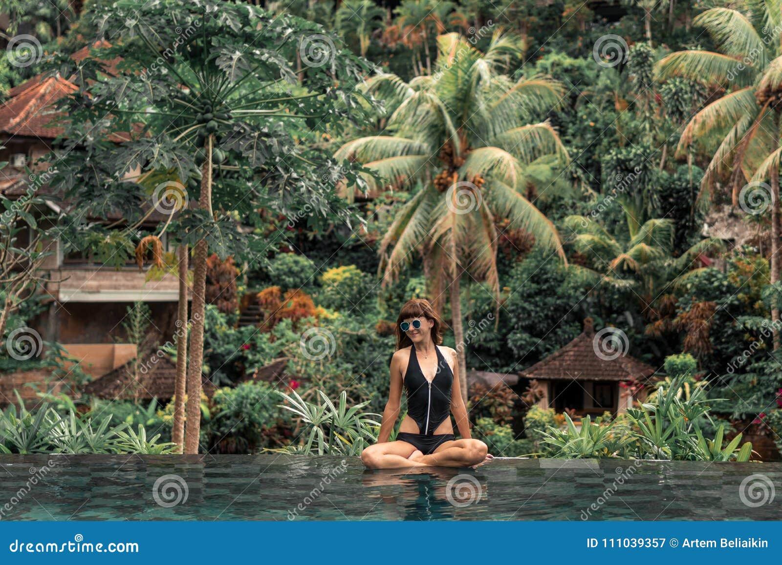 Mujer joven feliz en una piscina tropical del infinito Centro turístico de lujo en la isla de Bali