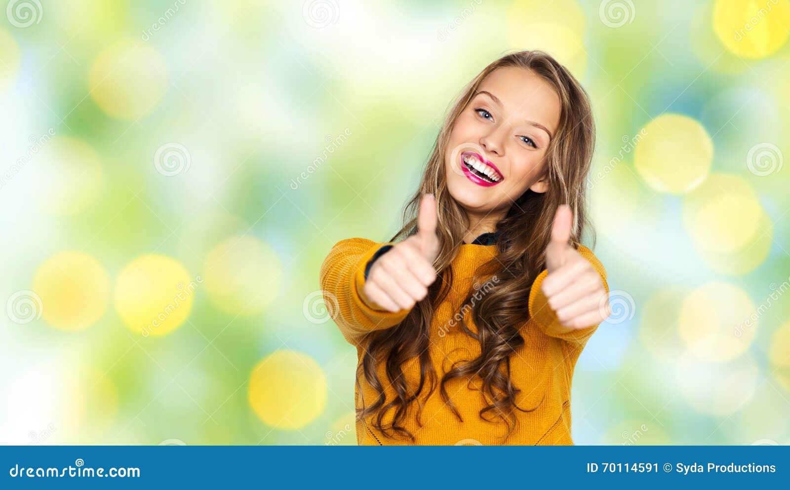 Chica adolescente alegre con pulgar arriba estudiando