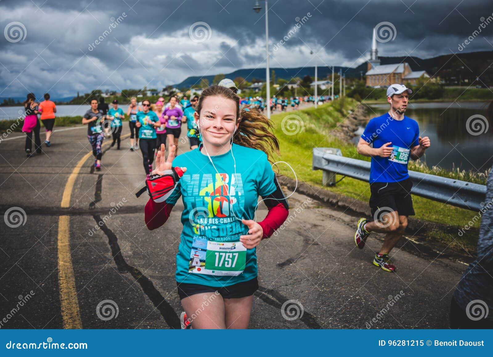 Mujer joven feliz que corre un 10K y que escucha una cierta música