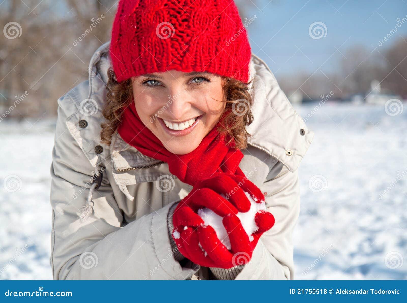Mujer joven feliz que juega lucha de la bola de nieve