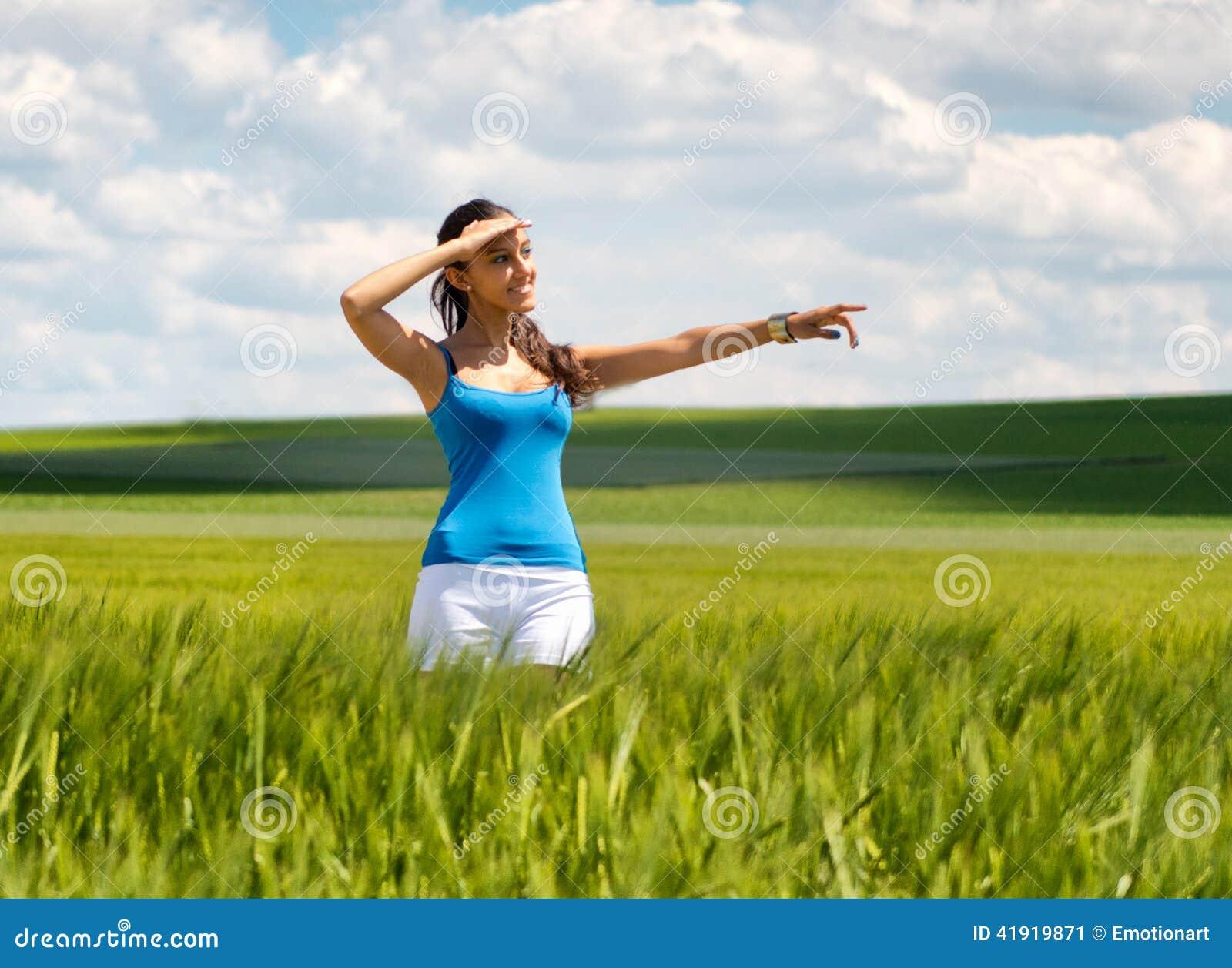 Mujer joven feliz que se coloca en señalar del campo