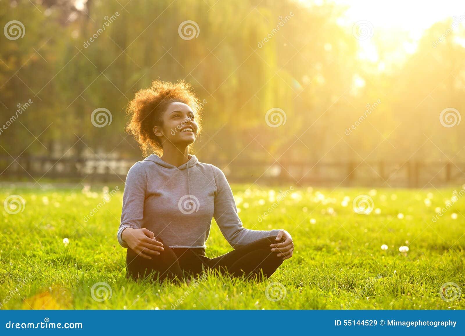 Mujer joven feliz que se sienta en la posición de la yoga