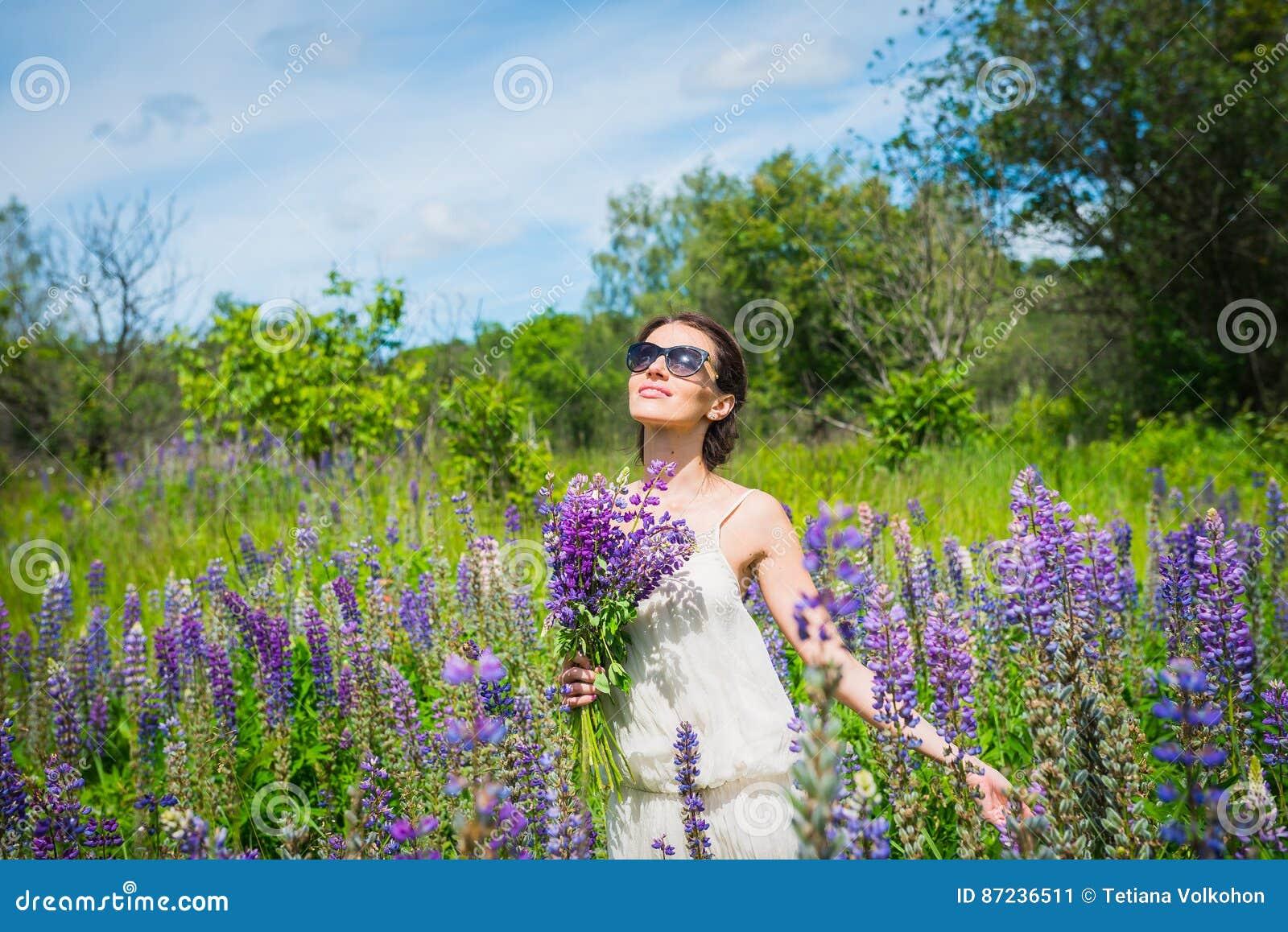 Mujer joven, feliz, situación entre el campo de los lupines violetas, sonriendo, flores púrpuras Cielo azul en el fondo Verano, c