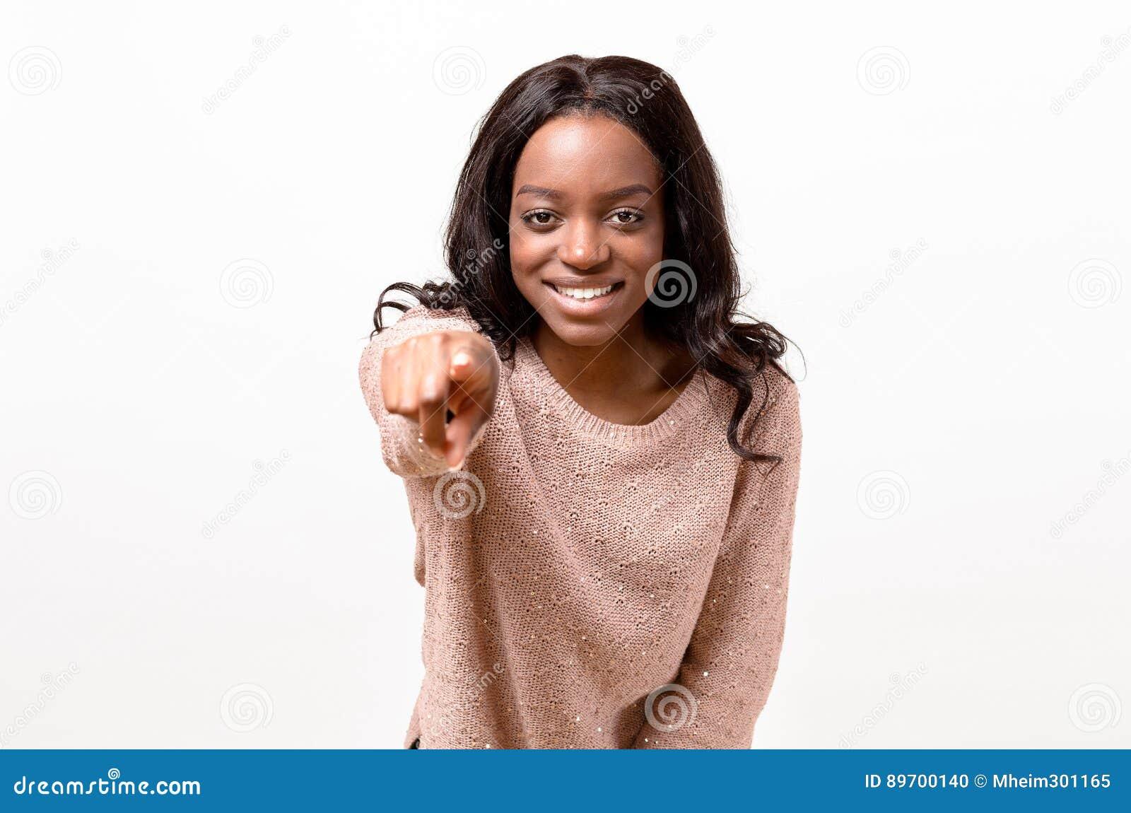 Mujer joven feliz sonriente que señala adelante