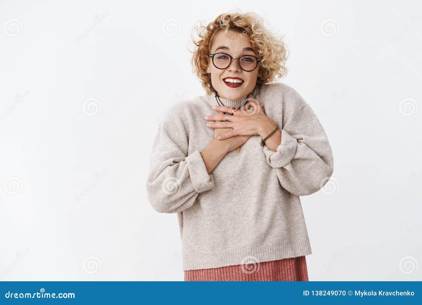 Mujer joven feliz y blanda sorprendida que recibe el regalo precioso encantador que lleva a cabo las manos en pecho en actitud ag