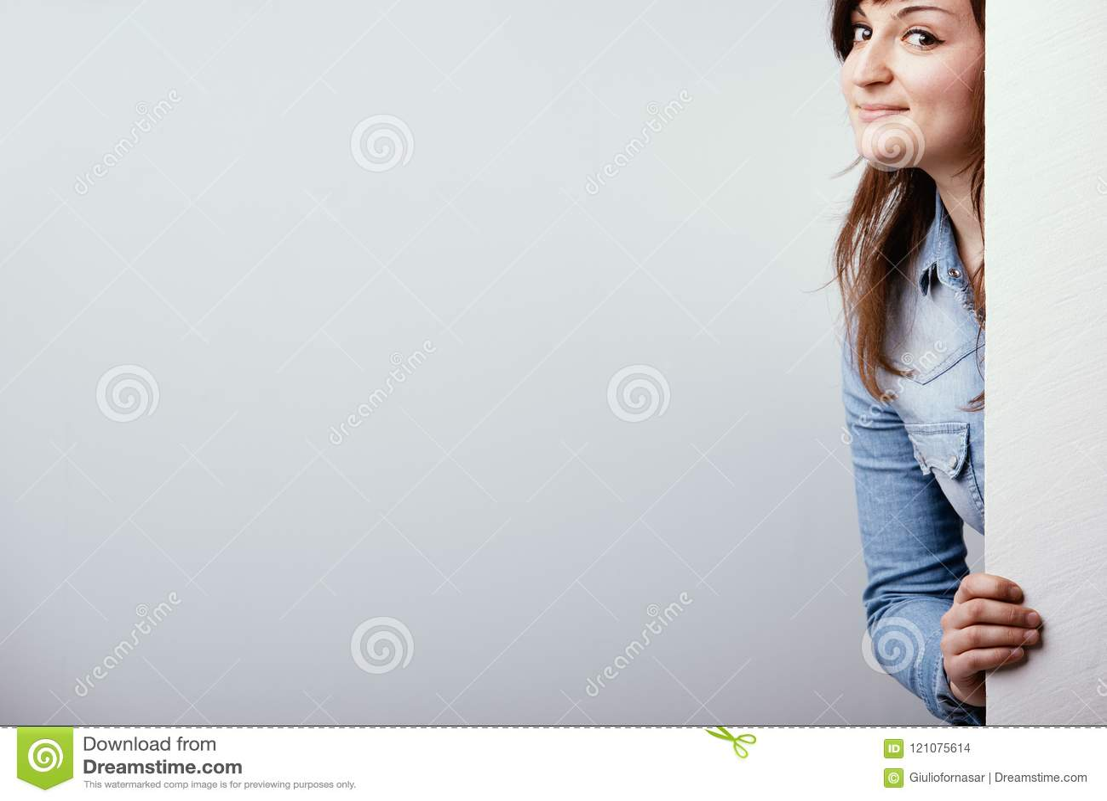 Mujer joven fresca que mira alrededor de una muestra