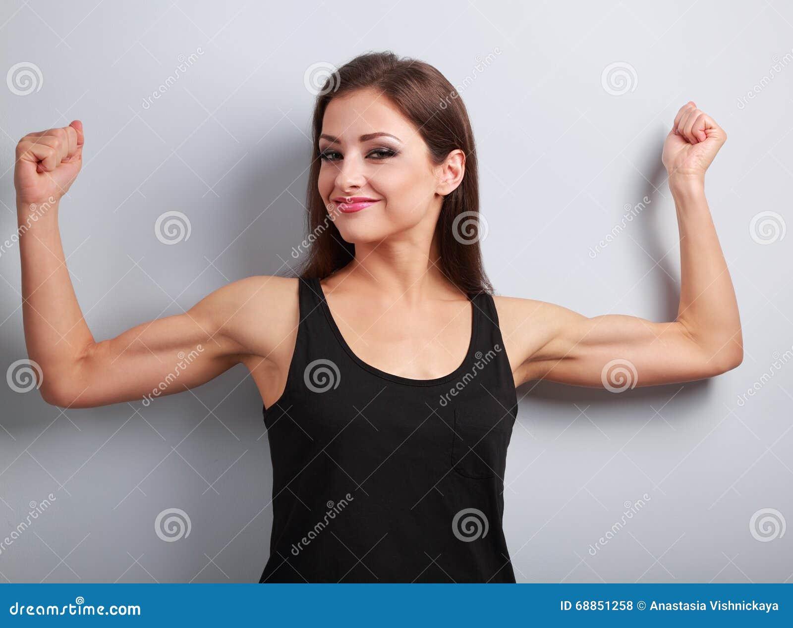 Mujer joven fuerte contenta que muestra el bíceps del músculo con la sonrisa encendido