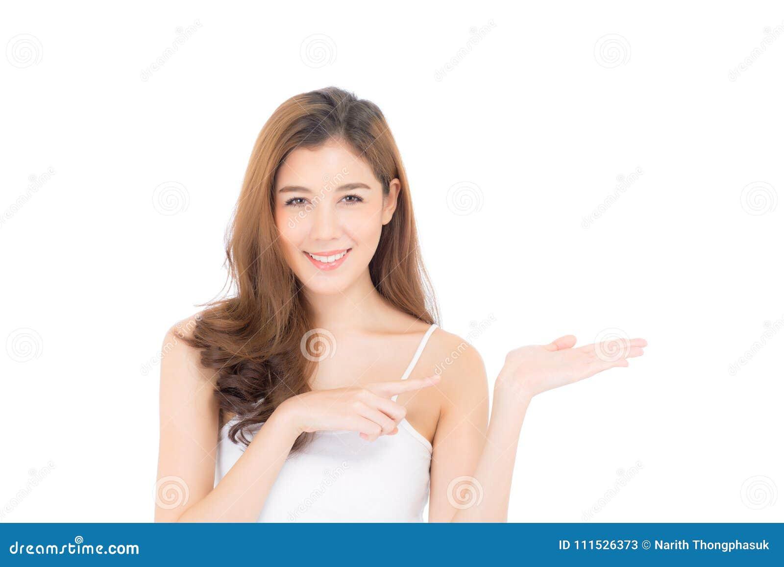 Mujer joven hermosa asiática que muestra con la piel limpia sana que presenta a algo el espacio vacío de la copia