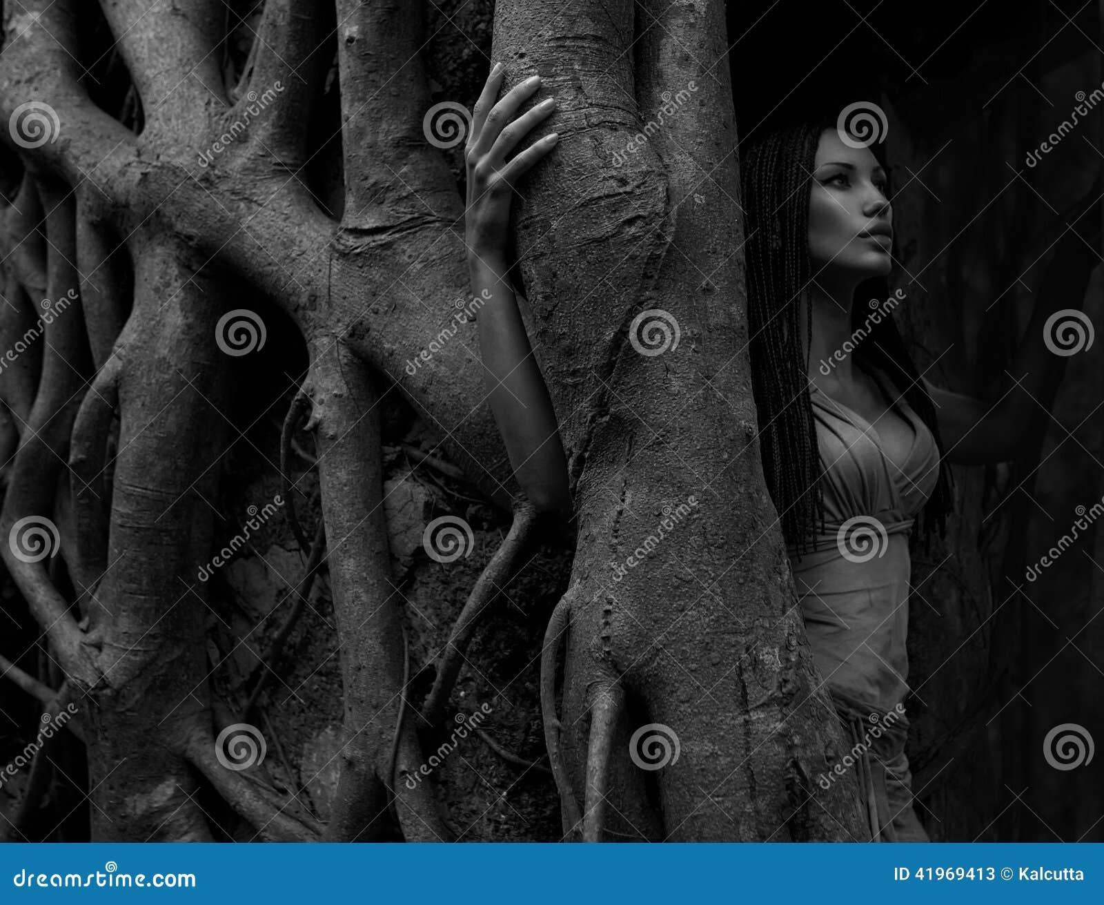 Mujer joven hermosa cerca del baniano en la selva tropical en Indi
