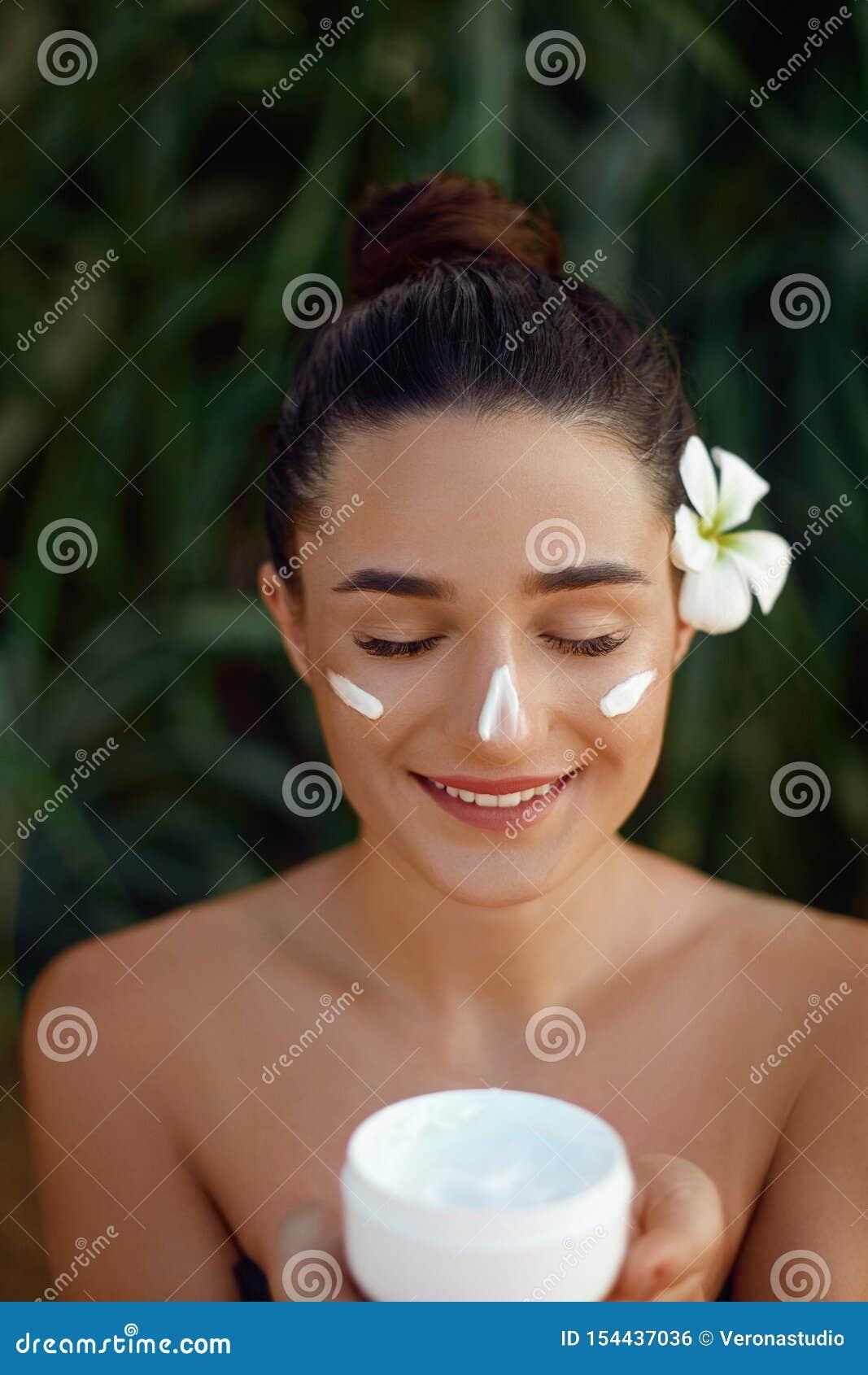 Mujer joven hermosa con crema hidratante en cara Crema cosmética de la botella de la tenencia de la muchacha Loción de aplicación