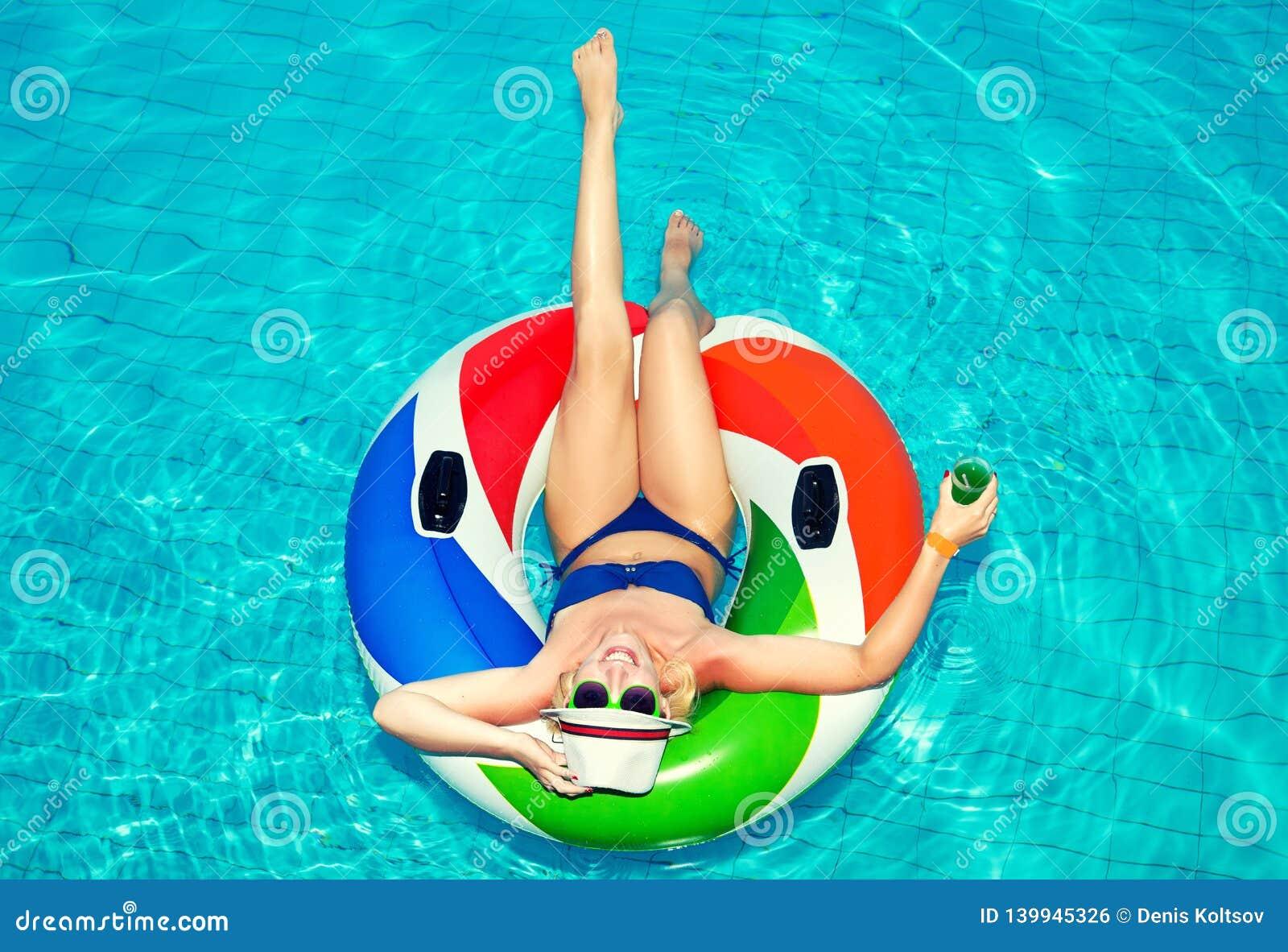 Mujer joven hermosa con el anillo inflable que se relaja en piscina y bebidas azules un cóctel