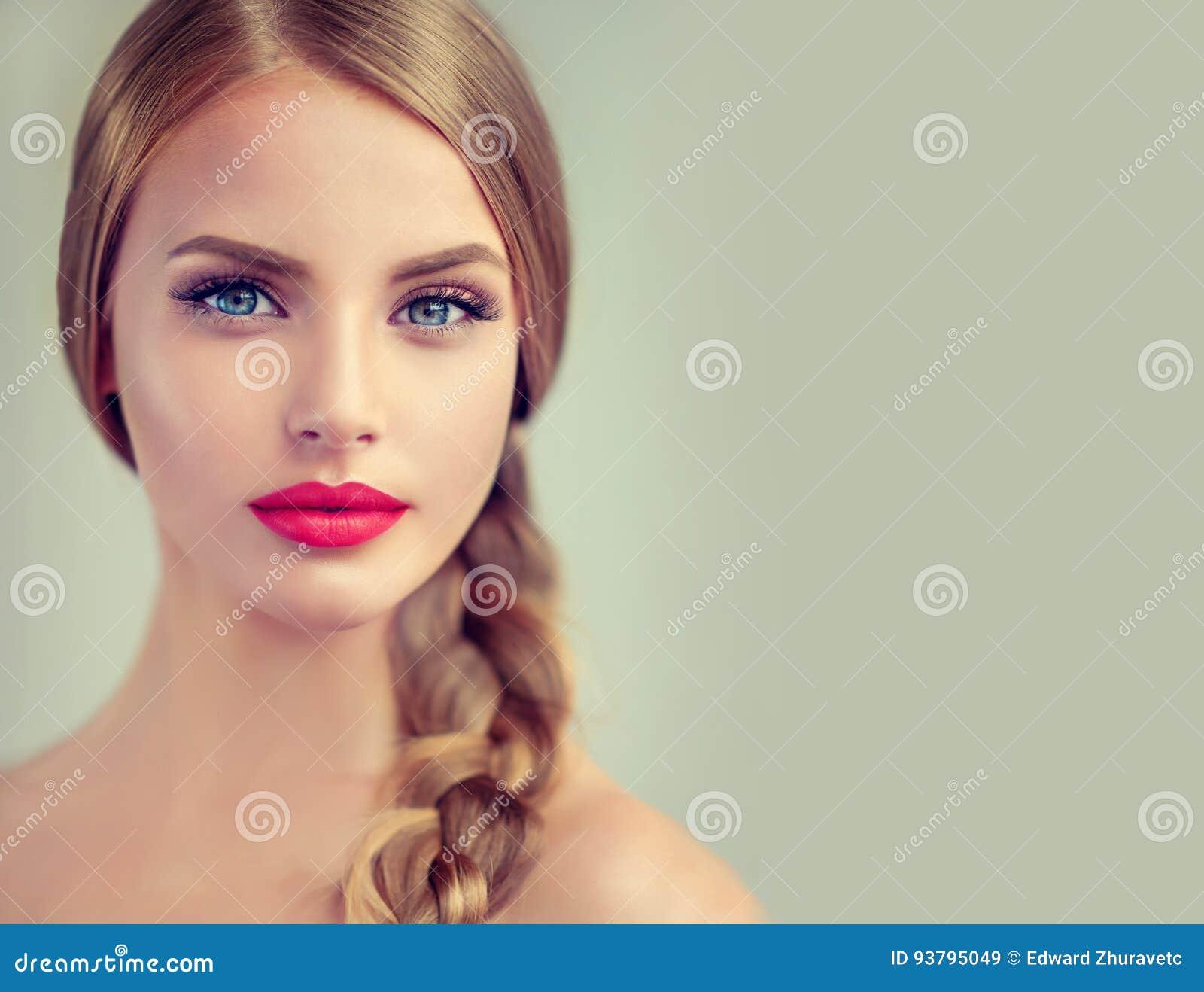 Mujer joven hermosa con el braidpigtail y pendientes grandes en ella