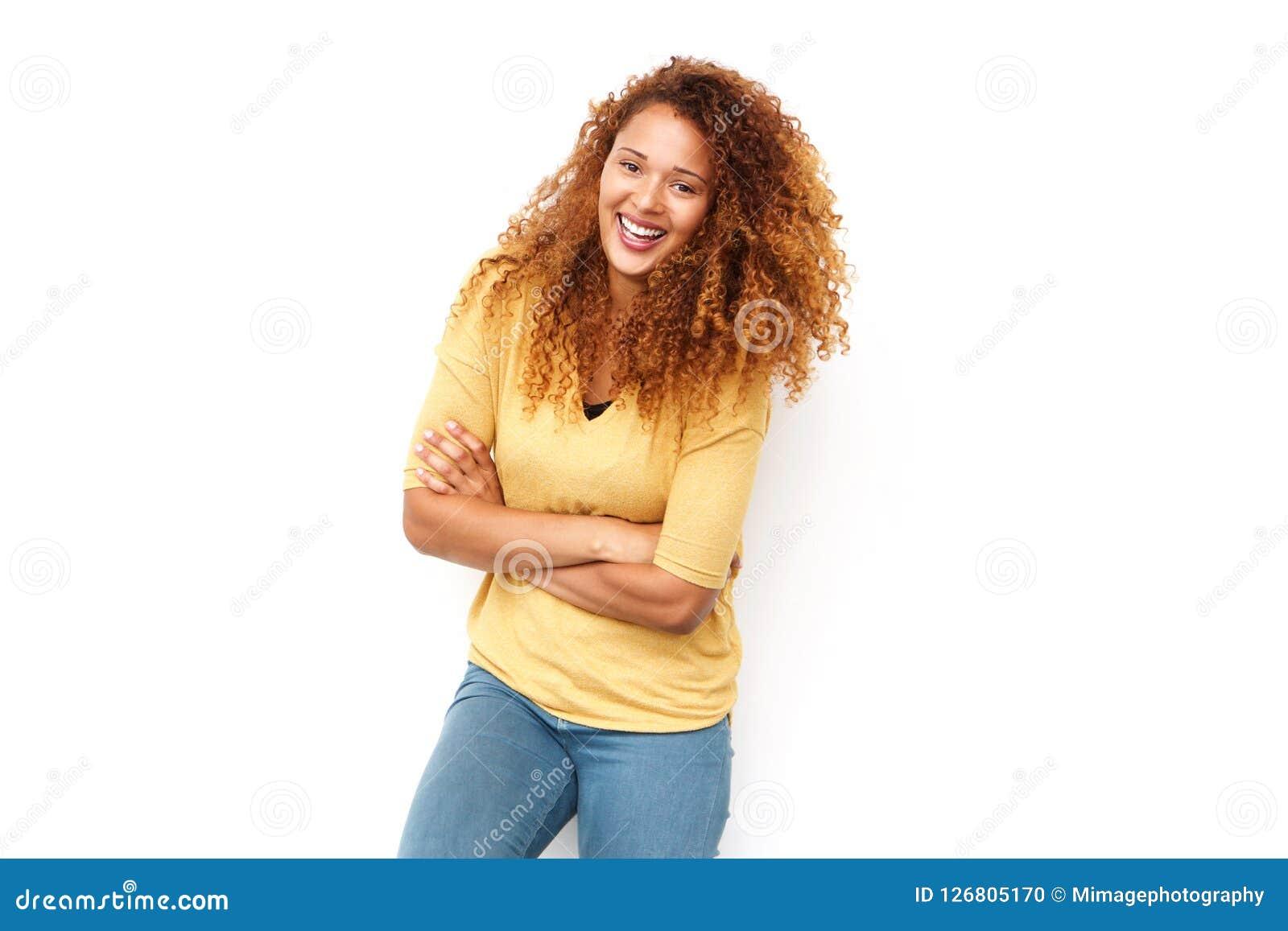 Mujer joven hermosa con el pelo rizado que ríe con los brazos cruzados contra el fondo blanco
