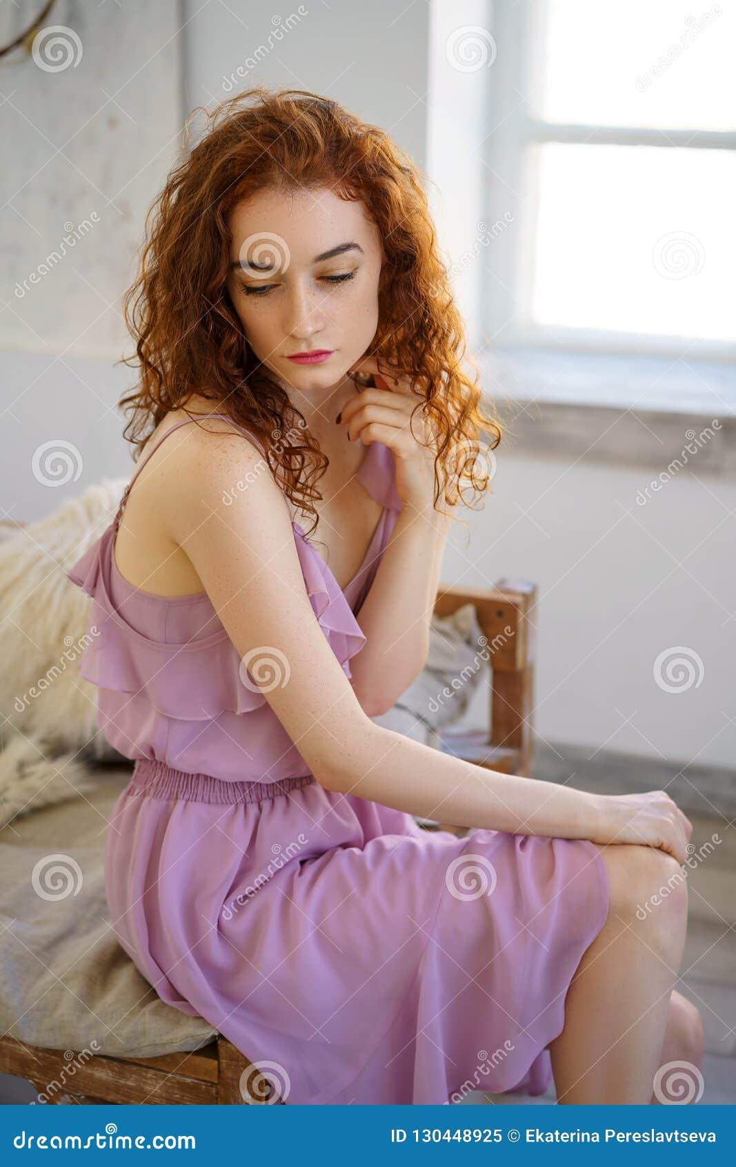 Mujer joven hermosa con el pelo rojo que se sienta en estudio