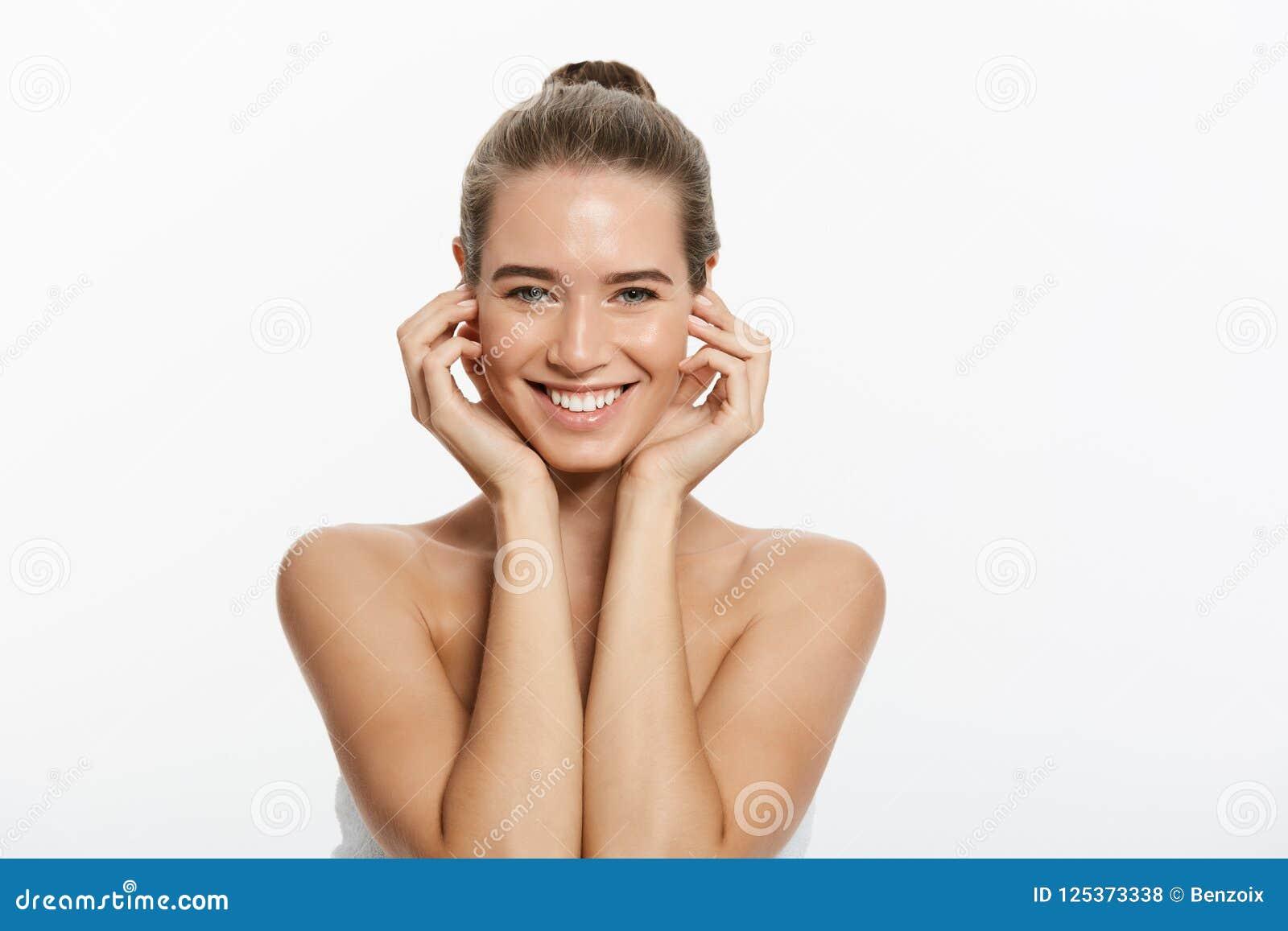 Mujer joven hermosa con la piel perfecta fresca limpia El retrato del modelo con desnudo natural compone, con la toalla en el cue
