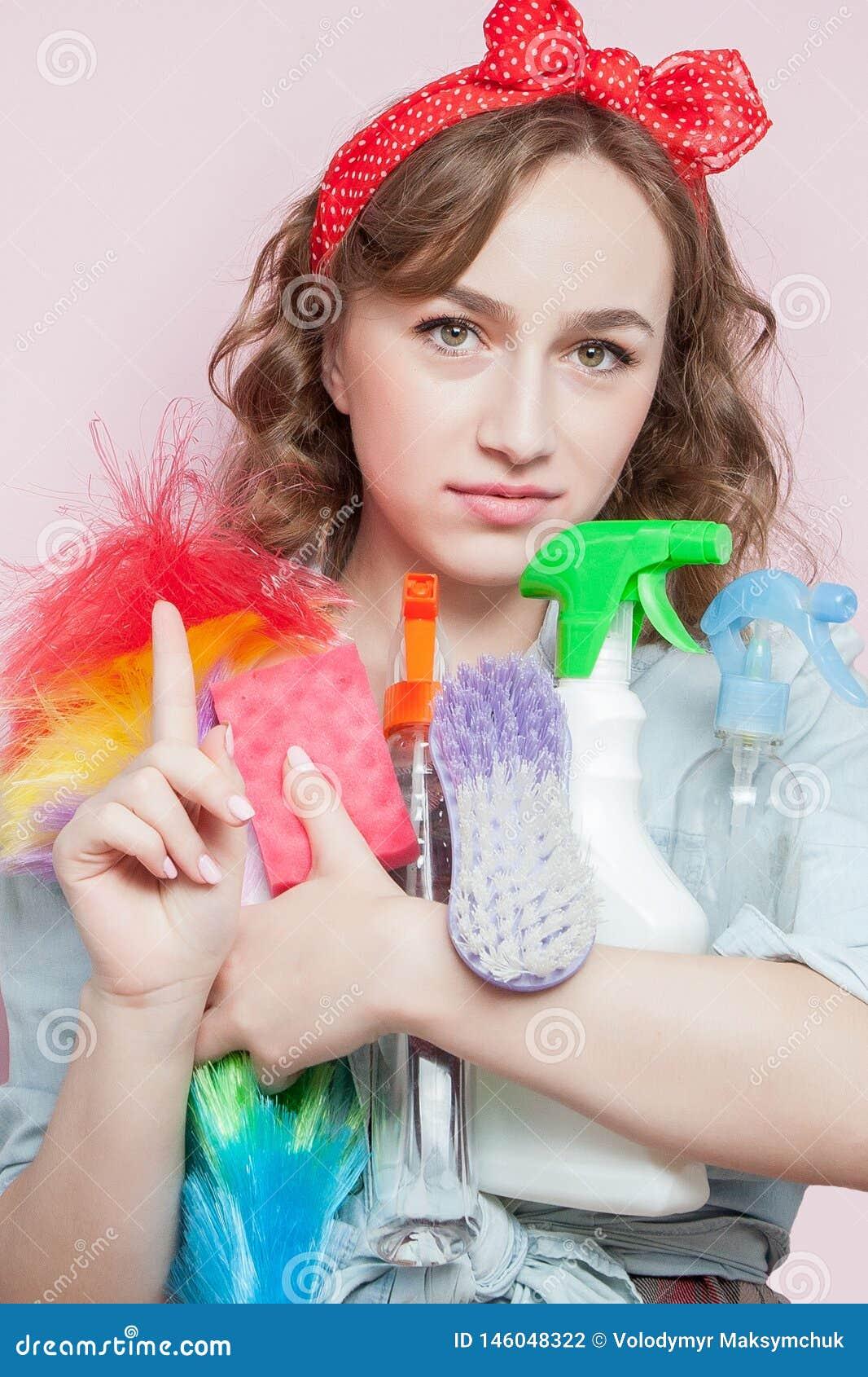 Mujer joven hermosa con maquillaje del perno-para arriba y peinado con las herramientas de limpieza en fondo rosado
