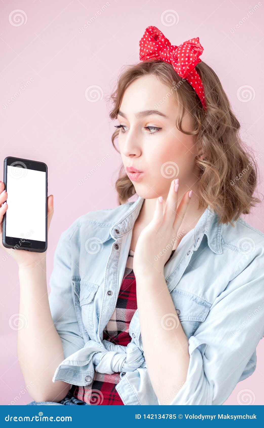 Mujer joven hermosa con maquillaje del perno-para arriba y peinado sobre fondo rosado con el teléfono móvil con el espacio de la