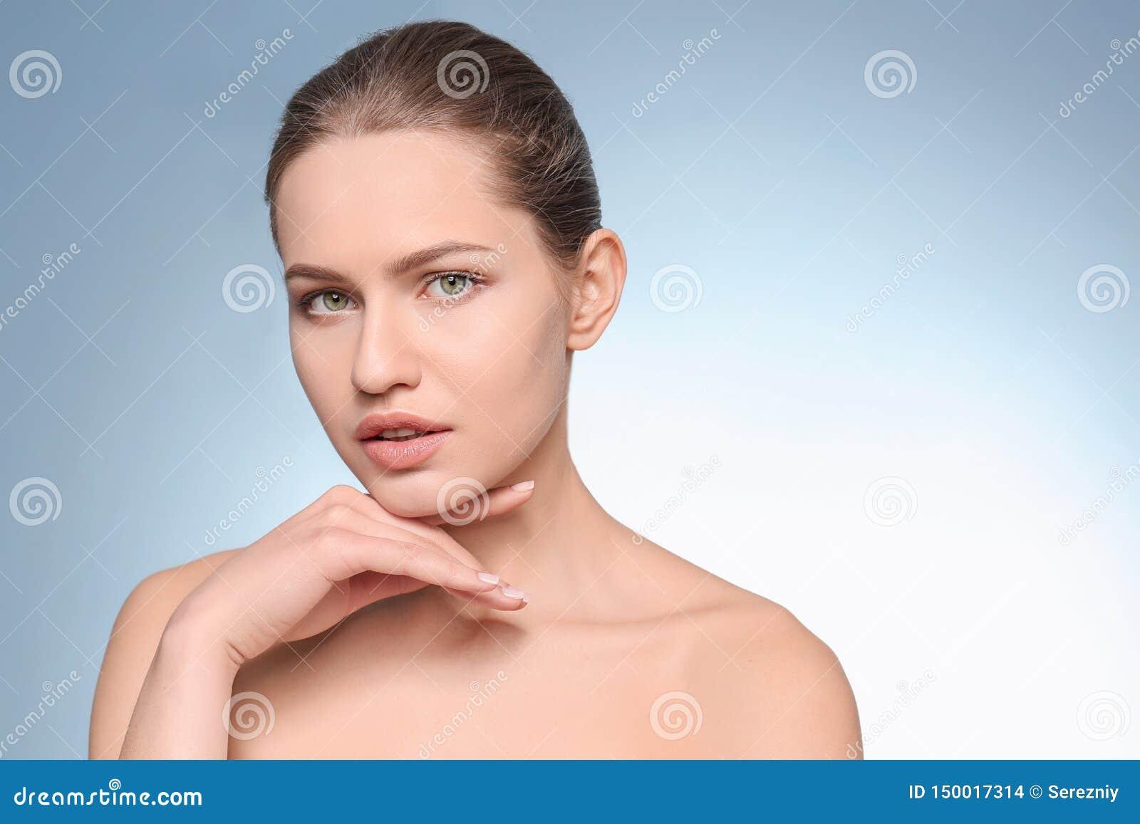 Mujer joven hermosa con maquillaje natural en fondo del color