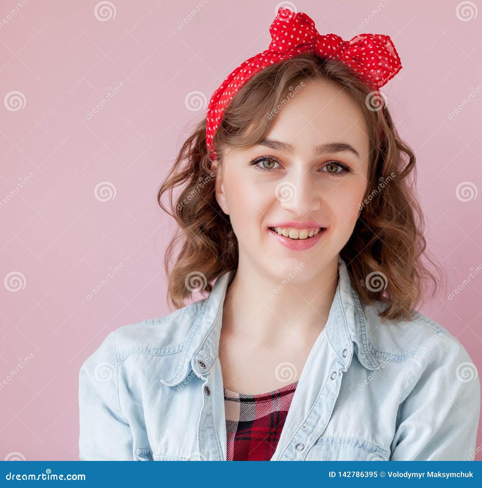 Mujer joven hermosa con maquillaje y el peinado del perno-para arriba Estudio tirado en fondo rosado