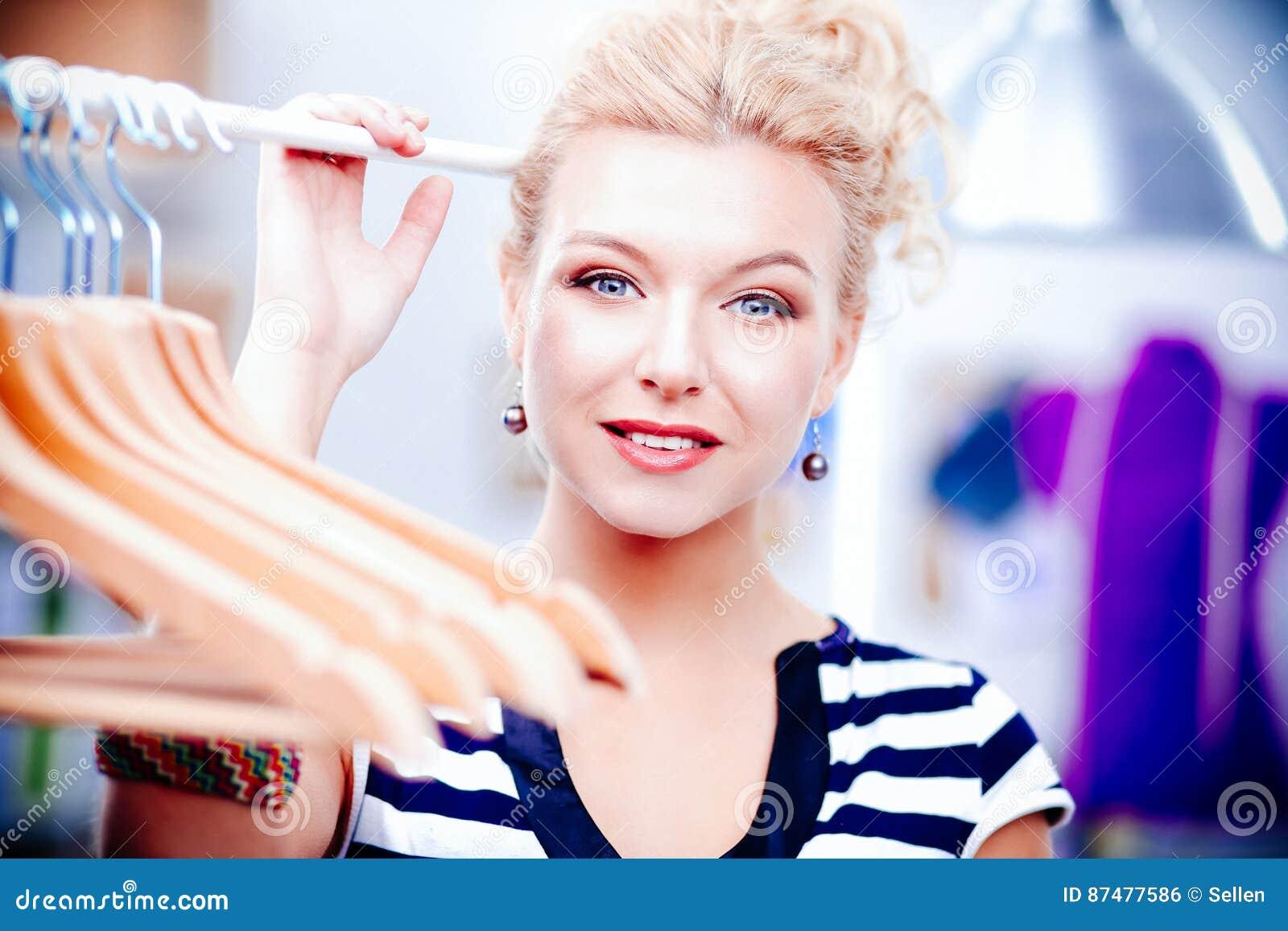 Mujer joven hermosa del estilista cerca del estante con las suspensiones