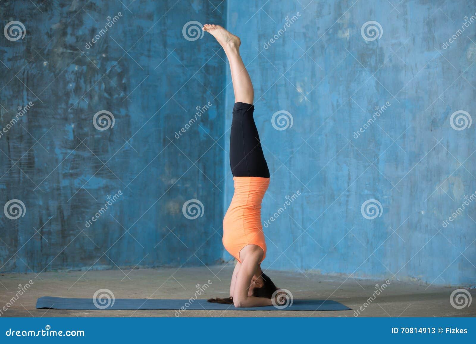 Mujer joven hermosa deportiva que hace el headstand