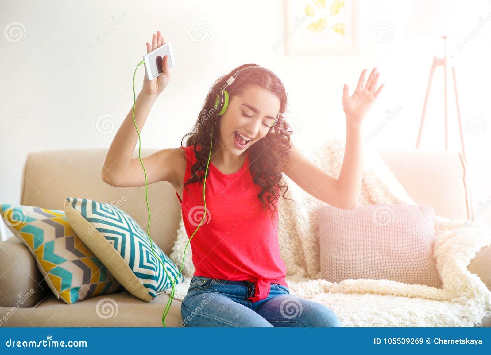 Mujer joven hermosa en auriculares que escucha la música en casa