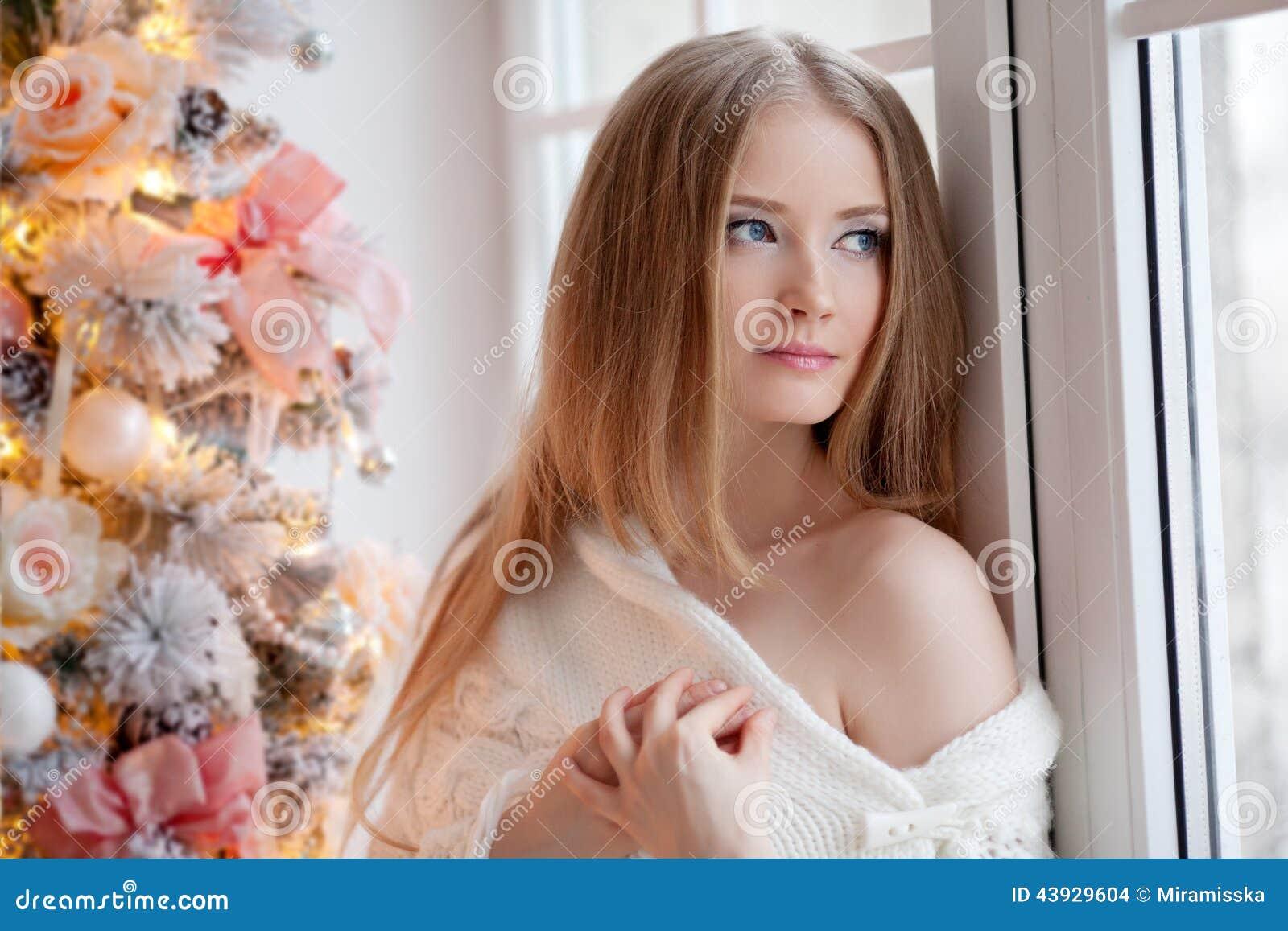 Mujer joven hermosa en blanco cerca del árbol de navidad Beautifu