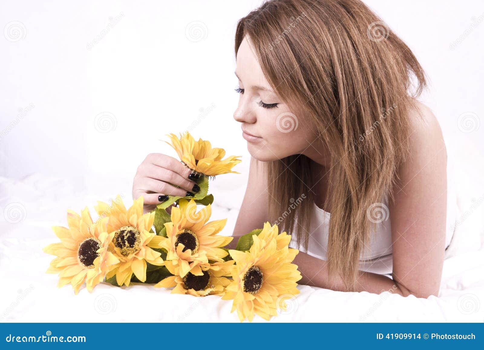 Mujer joven hermosa en cama con los girasoles