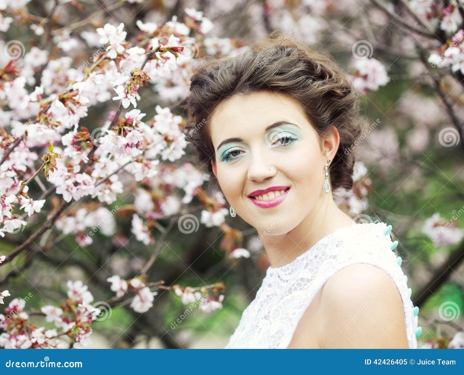 Mujer joven hermosa en el jardín de la primavera