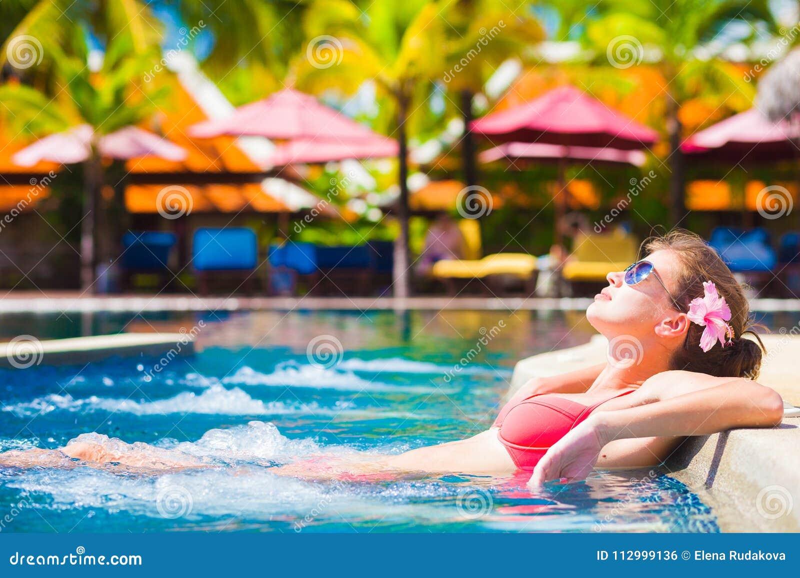 Mujer joven hermosa en gafas de sol en piscina de lujo del balneario
