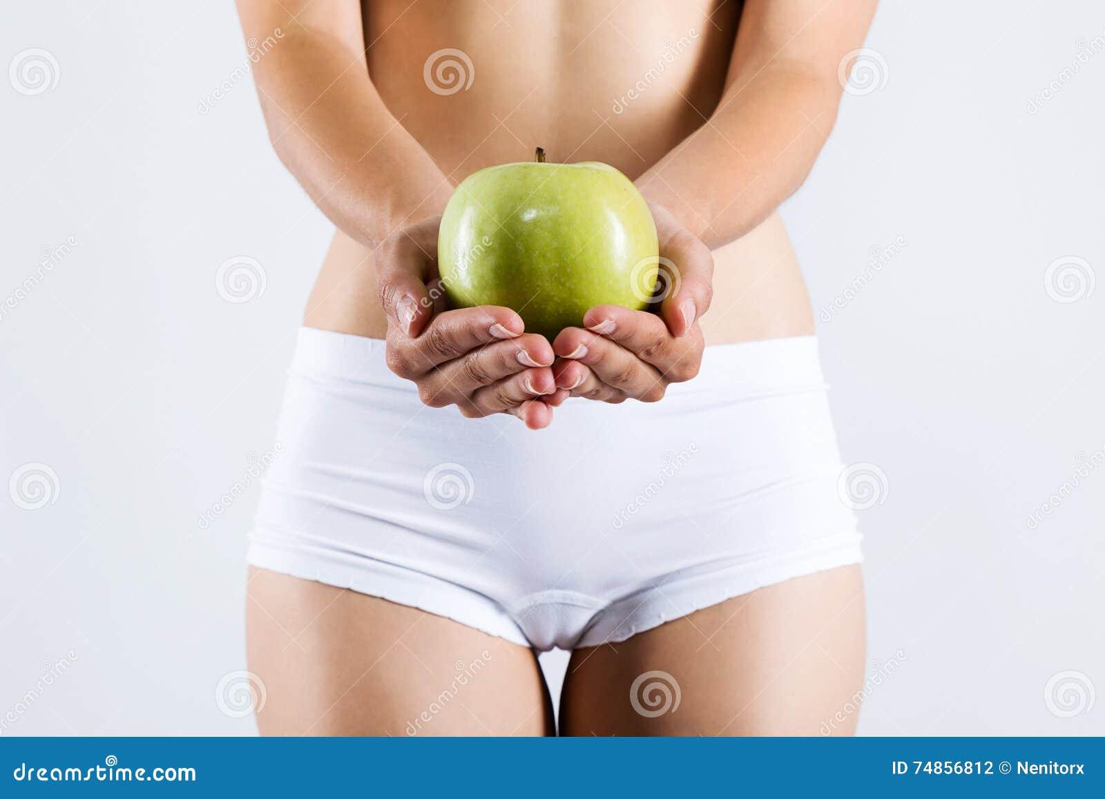Mujer joven hermosa en la ropa interior blanca que sostiene la manzana verde 2f09911041bb
