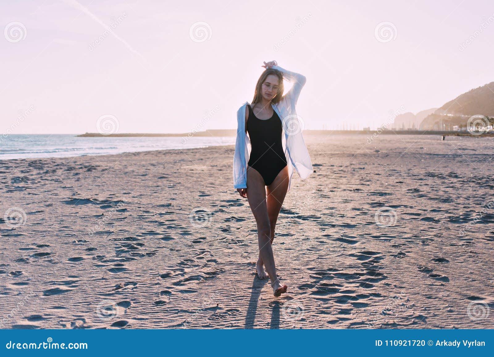 Mujer joven hermosa en traje de baño en la playa