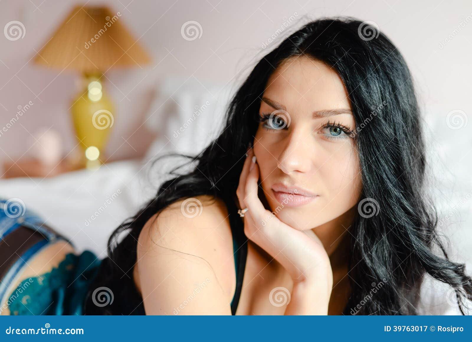 Mujer joven hermosa encantadora en la camisa de seda de la turquesa bonita que mira la cámara que miente en el retrato blanco del