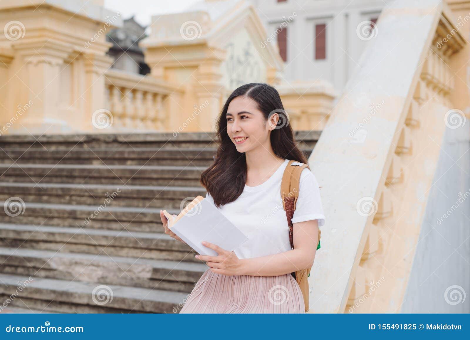 Mujer joven hermosa feliz con la mochila y el libro que se sientan en las escaleras al aire libre