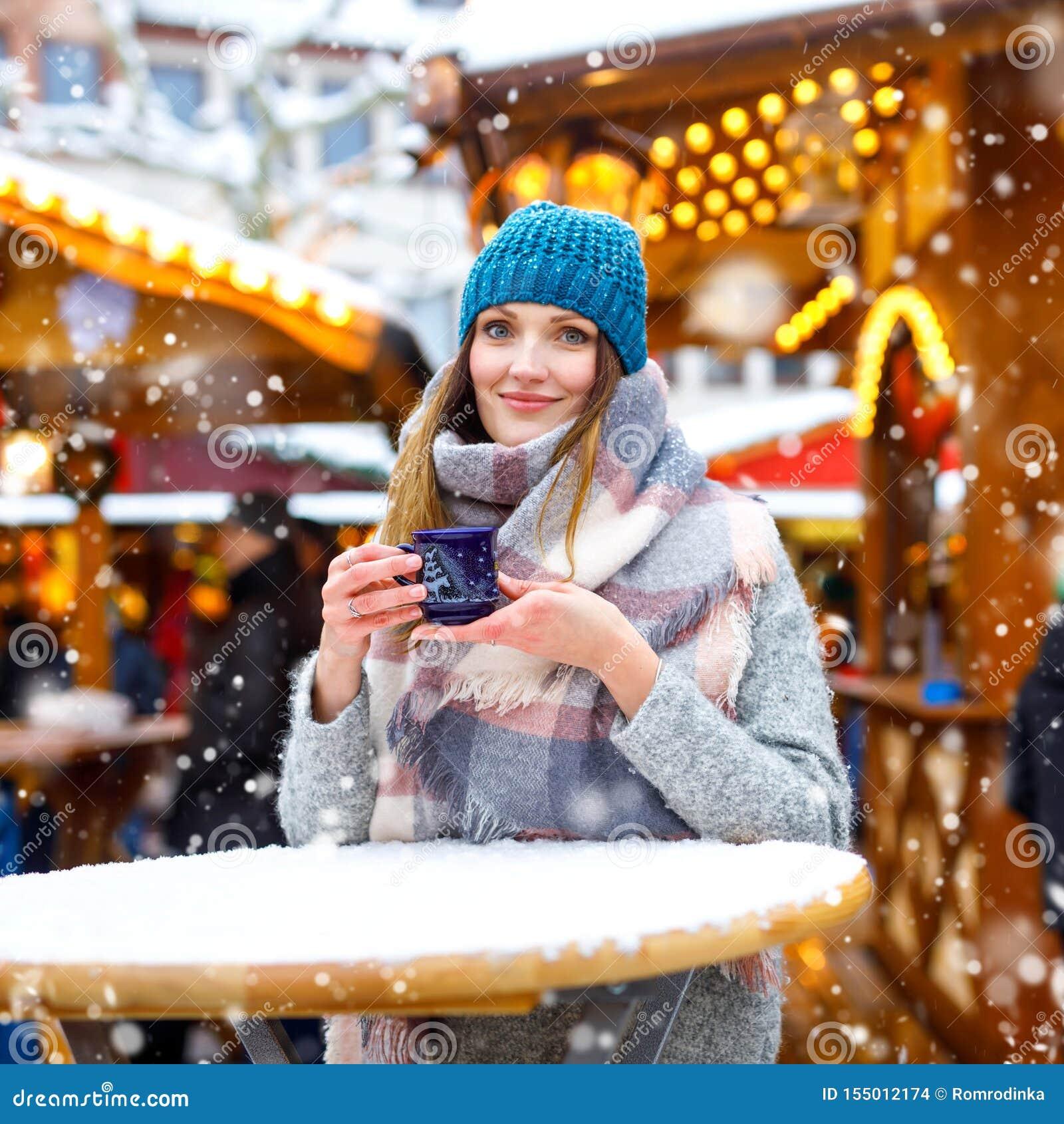 Mujer joven hermosa que bebe el sacador caliente, vino reflexionado sobre en mercado alem?n de la Navidad Muchacha feliz en ropa