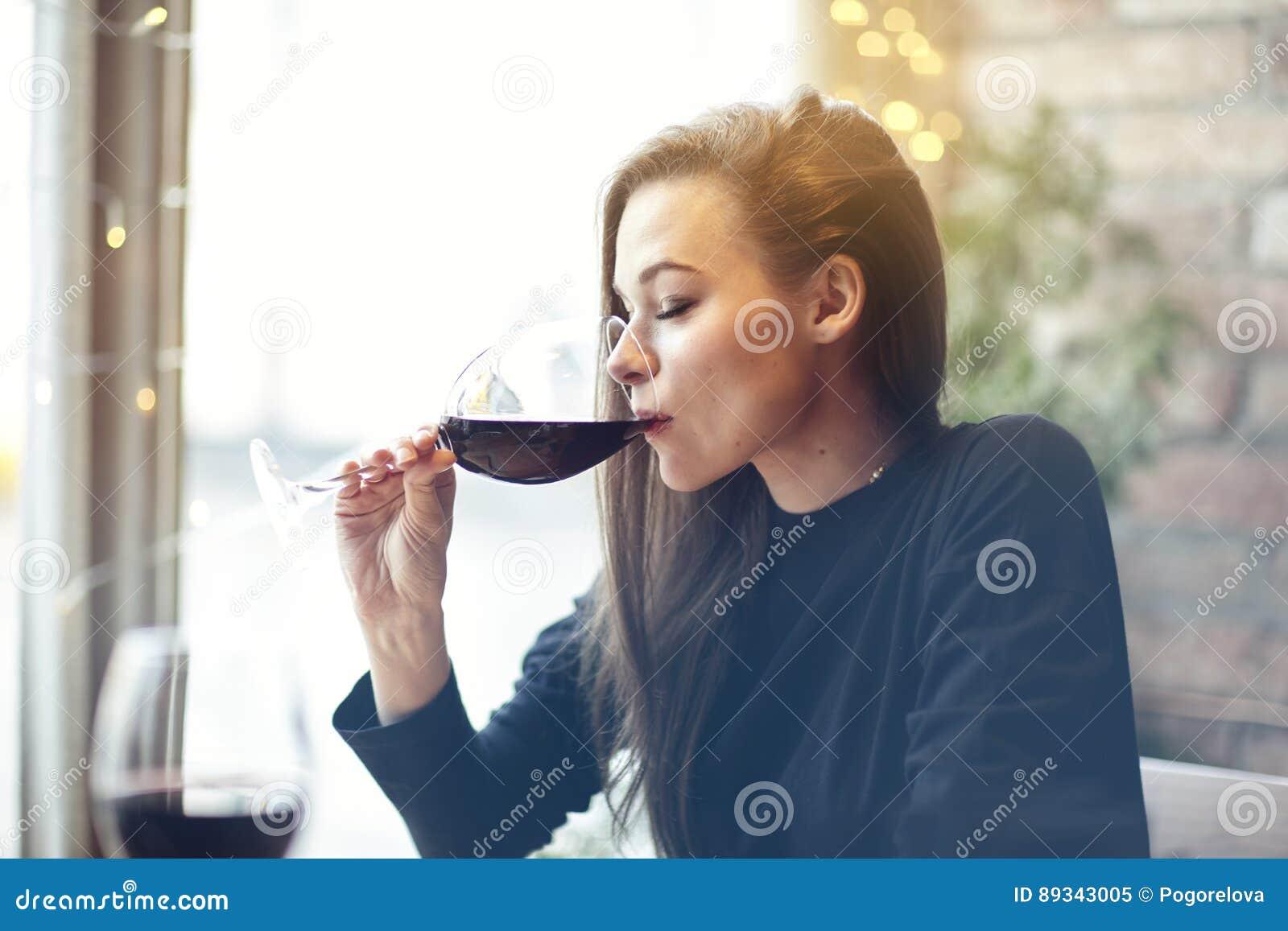 Mujer joven hermosa que bebe el vino rojo con los amigos en el café, retrato con la copa de vino cerca de la ventana Igualación d