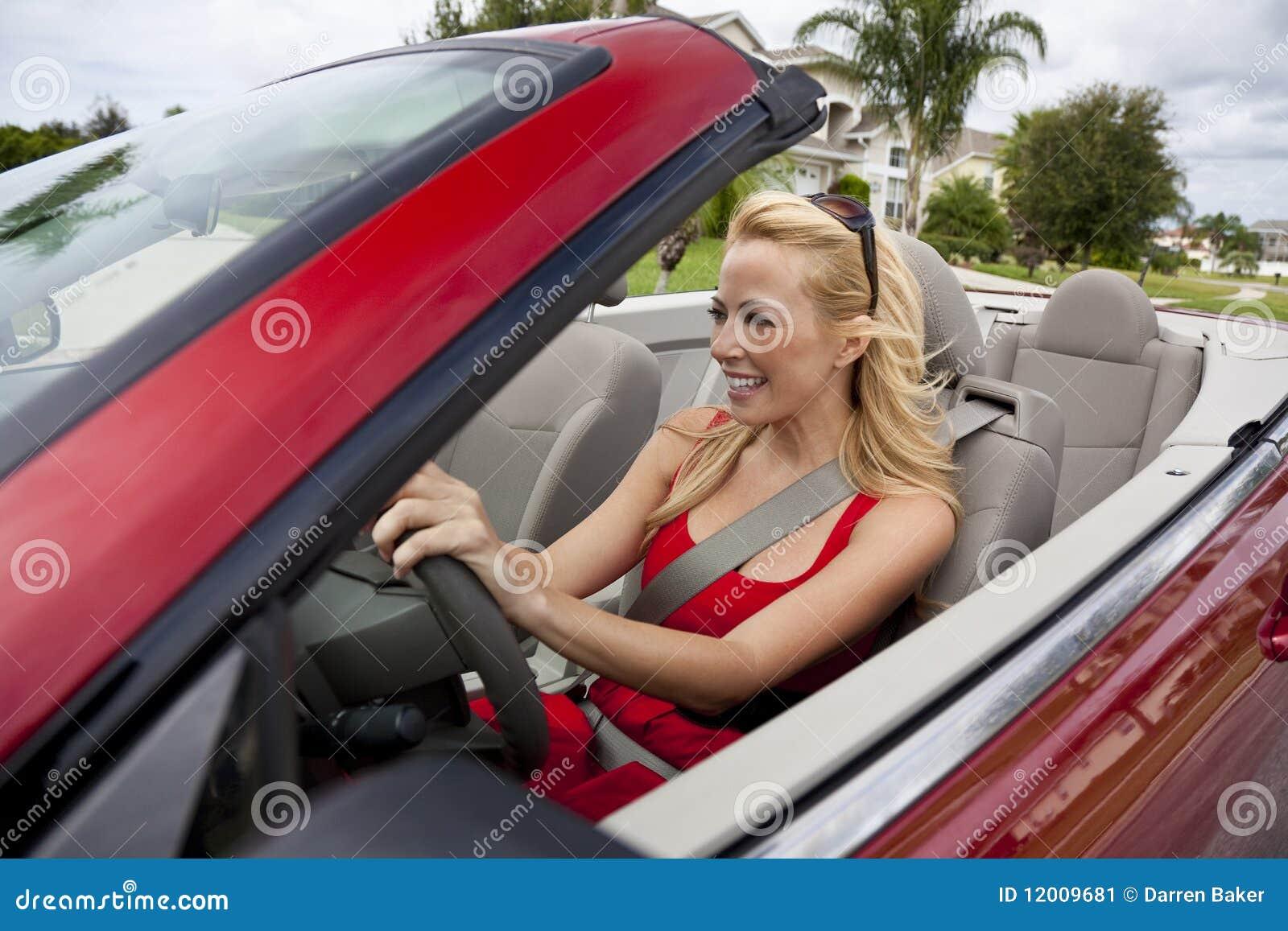 Mujer joven hermosa que conduce el coche convertible