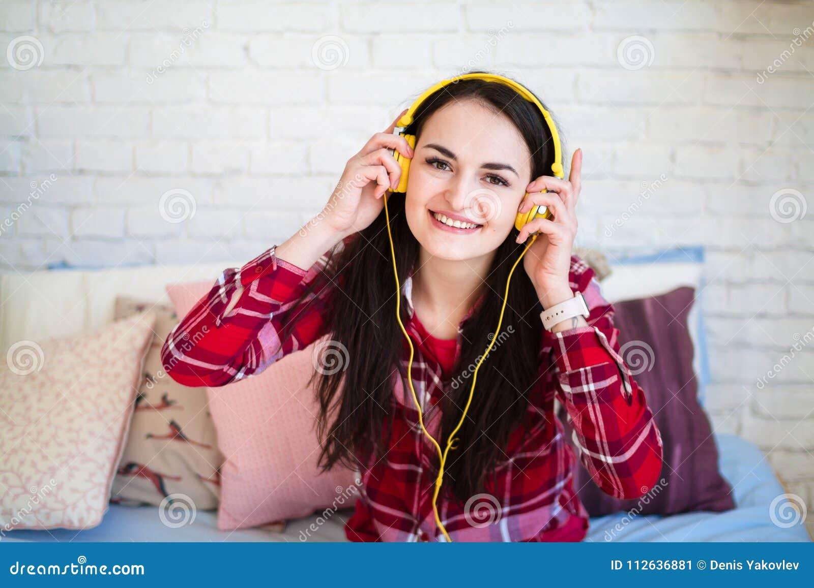 Mujer joven hermosa que escucha la música en auriculares en casa