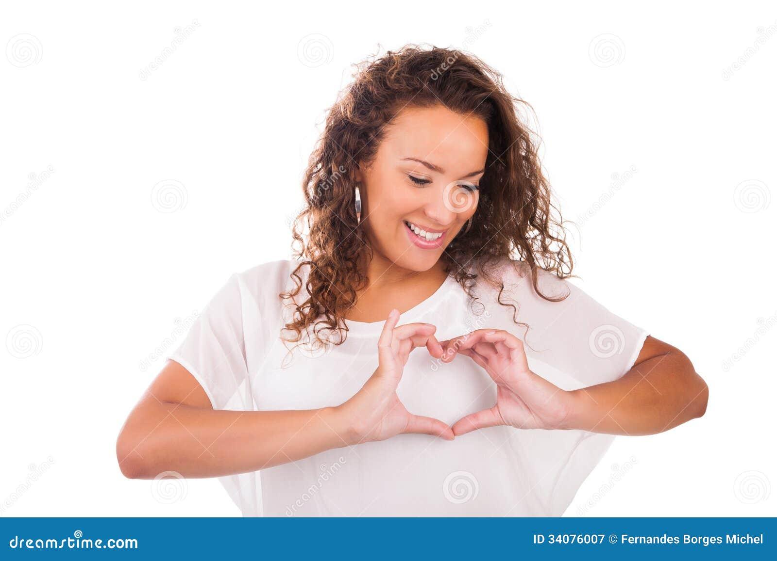 Mujer joven hermosa que hace un corazón con las manos