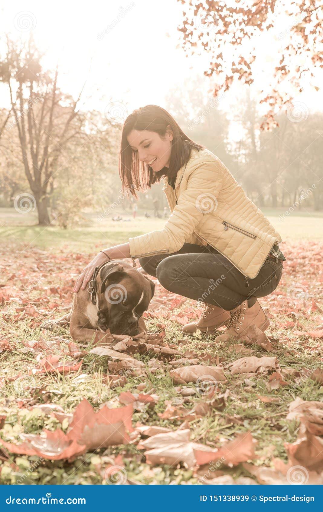 Mujer joven hermosa que juega con su perro en el bosque